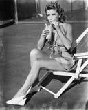 Junge Frau, die auf dem Riemenstuhl, an einem Getränk nippend sitzt (alle dargestellten Personen sind nicht längeres lebendes und Stockfoto