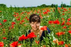 Junge Frau, die auf dem roten Mohnblumengebiet aufwirft Lizenzfreie Stockbilder