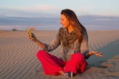Junge Frau, die auf dem Sand in der Wüste sitzt und auf Skype spricht Stockbild