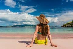 Junge Frau, die auf dem Sand am rosa Strand in Komodo-Insel, Indonesien sitzt Stockfotografie