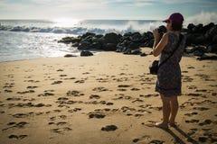Junge Frau, die auf dem sandigen Strand des atlantischen Ufers Fotos des schönen Meerblicks und der Surfer machend steht Stockbild