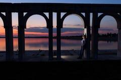 Junge Frau, die auf dem See bei Sonnenuntergang sich entspannt Lizenzfreie Stockbilder