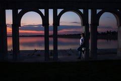 Junge Frau, die auf dem See bei Sonnenuntergang sich entspannt Stockbilder