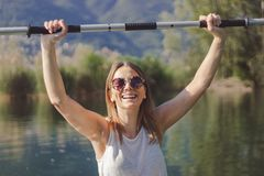 Junge Frau, die auf dem See Kayak f?hrt stockfoto