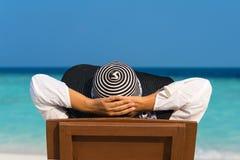Junge Frau, die auf dem Seestrand sich entspannt Lizenzfreie Stockfotografie