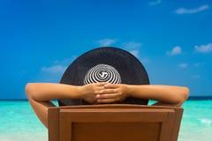 Junge Frau, die auf dem Seestrand sich entspannt Stockfotos
