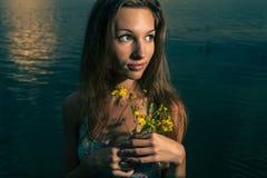 Junge Frau, die auf dem Sonnenuntergangpanorama von Fluss aufwirft Stockbilder