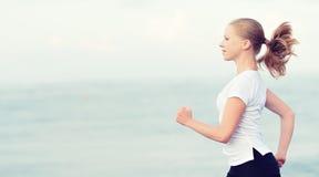 Junge Frau, die auf dem Strand auf der Küste des Meeres läuft Lizenzfreie Stockfotos