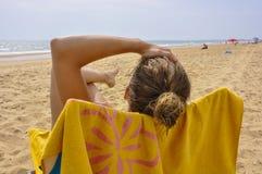 Junge Frau, die auf dem Strand ein Sonnenbad nimmt Stockbild