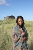 Junge Frau, die auf dem Strand eingewickelt in der Decke steht Stockbild