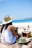 Junge Frau, die auf dem Strand isst Stockfotografie