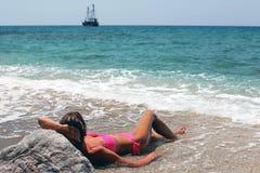Junge Frau, die auf dem Strand liegt Lizenzfreie Stockfotos