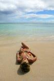Junge Frau, die auf dem Strand liegt Lizenzfreies Stockbild