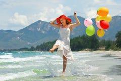 Junge Frau, die auf dem Strand mit bunten Ballonen spielt lizenzfreies stockfoto