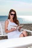 Junge Frau, die auf dem Strand sich entspannt Stockfotografie