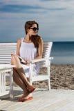 Junge Frau, die auf dem Strand sich entspannt Stockbild