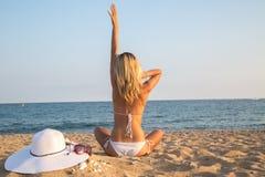 Junge Frau, die auf dem Strand sitzt Stockfotos