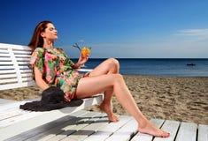 Junge Frau, die auf dem Strand stillsteht stockfotos