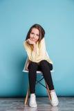 Junge Frau, die auf dem Stuhl über blauem Hintergrund sitzt Lizenzfreies Stockbild