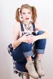 Junge Frau, die auf dem Stuhl sitzt Stockbild