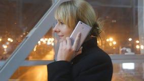 Junge Frau, die auf dem Telefon und dem Weg in der Nacht Innen spricht Attraktives Mädchen, das über Mobiltelefon spricht Abschlu stock video footage