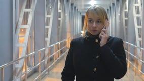 Junge Frau, die auf dem Telefon und dem Weg in der Nacht Innen spricht Porträt des attraktiven Mädchens sprechend über Mobiltelef stock video