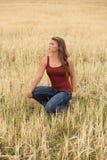 Junge Frau, die auf dem Weizengebiet aufwirft Lizenzfreie Stockfotografie