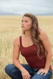 Junge Frau, die auf dem Weizengebiet aufwirft Stockbild