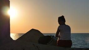 Junge Frau, die auf den Felsen sitzt und das Sonnenuntergangmeer betrachtet Stockfotos