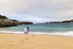 Junge Frau, die auf den Sand eines schönen Strandes geht stockbild