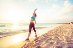 Junge Frau, die auf den Strand ausdehnt Lizenzfreie Stockfotos