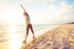 Junge Frau, die auf den Strand ausdehnt Lizenzfreies Stockfoto