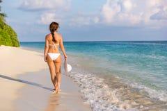 Junge Frau, die auf den Strand geht Lizenzfreie Stockbilder