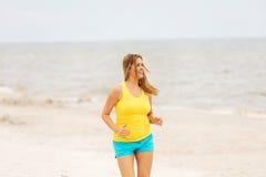 Junge Frau, die auf den Strand läuft lizenzfreie stockfotos