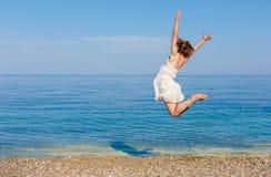Junge Frau, die auf den Strand springt Stockfotografie