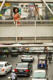 Junge Frau, die auf der Überführung über einer beschäftigten Landstraße in der Metropole steht Lizenzfreie Stockfotos