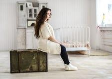 Junge Frau, die auf der alten Tasche sitzt Stockfotos