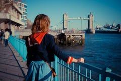 Junge Frau, die auf der Bank der Themse steht Lizenzfreie Stockfotos