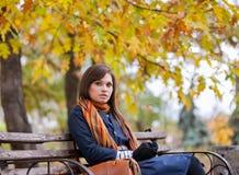 Junge Frau, die auf der Bank sitzt lizenzfreie stockfotografie