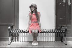 Junge Frau, die auf der Bank sitzt Stockfotos