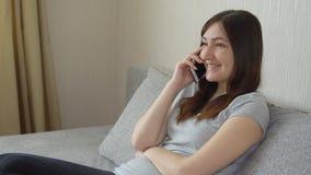 Junge Frau, die auf der Couch sitzt und am Telefon spricht stock footage
