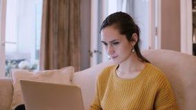 Junge Frau, die auf der Couch am Wohnzimmer sitzt und Laptop verwendet Frau, die das Internet und das Lächeln surft stock footage