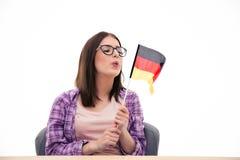 Junge Frau, die auf der deutschen Flagge durchbrennt Lizenzfreie Stockbilder