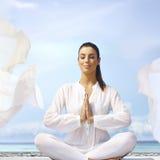 Junge Frau, die auf der Küste meditiert Lizenzfreie Stockfotografie