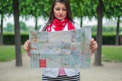 Junge Frau, die auf der Karte dem Stadtpark Paris, Frankreich betrachtet Lizenzfreies Stockfoto