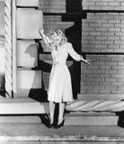 Junge Frau, die auf der Leiste eines Gebäudes steht und gefürchtet schaut (alle dargestellten Personen sind nicht längere lebende stockfotografie