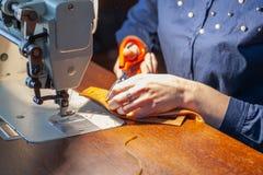 Junge Frau, die auf der Nähmaschine herstellt stockfotos