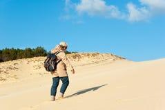 Junge Frau, die auf der Sanddüne klettert Lizenzfreie Stockfotos
