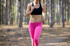 Junge Frau, die auf der Spur in der schönen wilden Kiefer Forest Active Lifestyle Concept läuft Raum für Text Lizenzfreie Stockfotografie