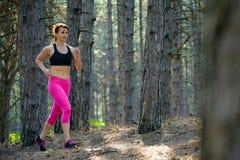 Junge Frau, die auf der Spur in der schönen wilden Kiefer Forest Active Lifestyle Concept läuft Raum für Text Lizenzfreie Stockbilder
